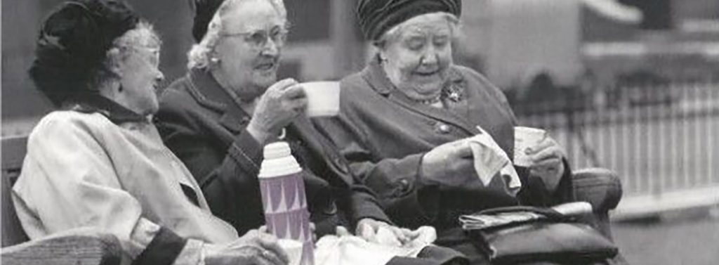 Picture of elderley ladies on a partk bench enjoying a cuppa and a laugh