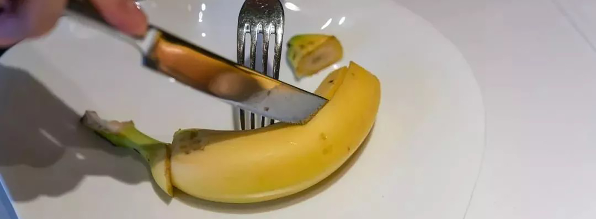 How to eat a banana in a posh restaurant. First cut off both ends, then insert the knife into the skin and slit from stem to stern. FInally reveal the flesh and cut into bite-sized chunks, as you eat daintily with a fork.